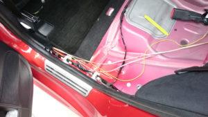 配線通しを使って、トランク側にスピーカーケーブルとサブウーハーのバッテリー電源用の配線を通します